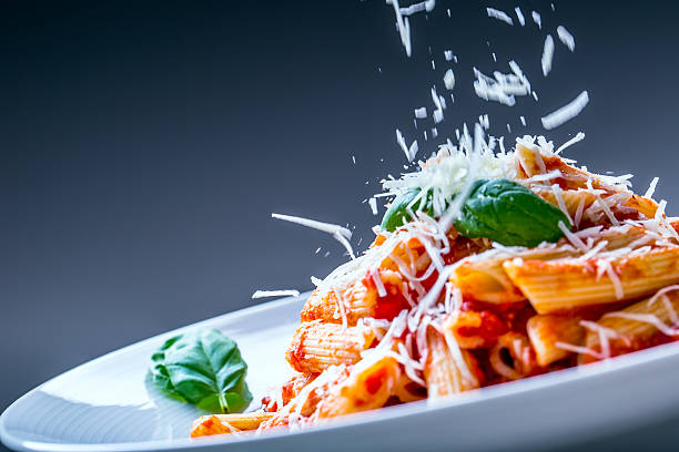 Pasta Penne with Tomato Bolognese Sauce, Parmesan Cheese and Basil. stock photo