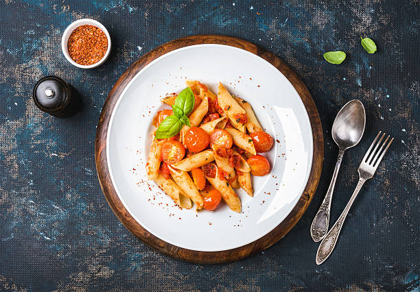 Pasta penne with tomato sauce, fresh basil and roasted tomatoes Pasta penne with tomato sauce, fresh basil and roasted tomatoes. Old painted dark plywood background, top view, horizontal composition penne stock pictures, royalty-free photos & images