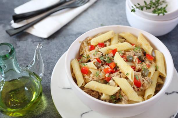 pasta penne mit thunfisch, paprika, olivenöl und verschließer - kaper stock-fotos und bilder