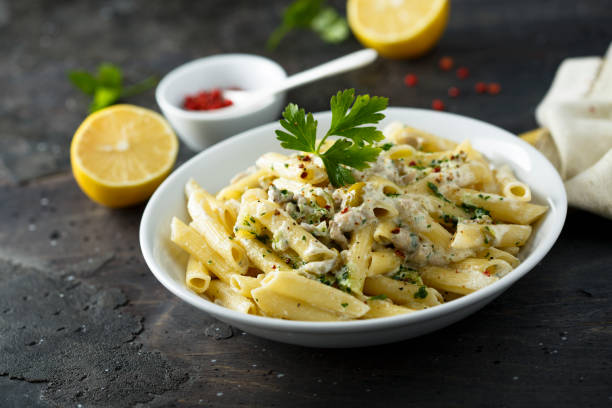 Pasta Pasta with olives and lemon sauce penne stock pictures, royalty-free photos & images