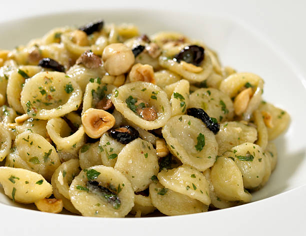 pasta pasta plate with nuts isolated on white orecchiette stock pictures, royalty-free photos & images