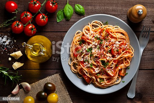 Pasta with tomato sauce shot from above on rustic wood table. Some ingredients for cooking pasta like tomatoes, olive oil, basil, parmesan cheese and a pepper mill are around the plate. DSRL low key studio photo taken with Canon EOS 5D Mk II and Canon EF 100mm f/2.8L Macro IS USM