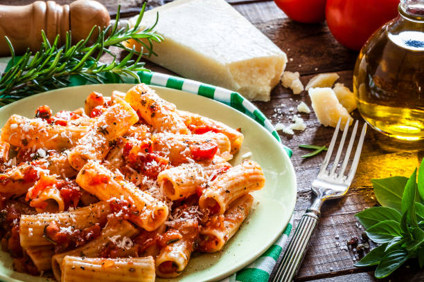 pasta plate shot on rustic wooden table - italian food stock photos and pictures