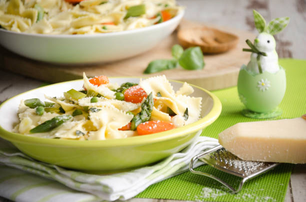 Pasta primavera for Easter Fresh bow-tie pasta served on a green plate with carrot,asparagus, onions, peas and parmesan with a bunny in egg for Easter primavera stock pictures, royalty-free photos & images