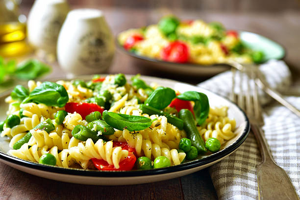 Pasta primavera on a vintage plates. Pasta primavera on a vintage plates on wooden background. primavera stock pictures, royalty-free photos & images