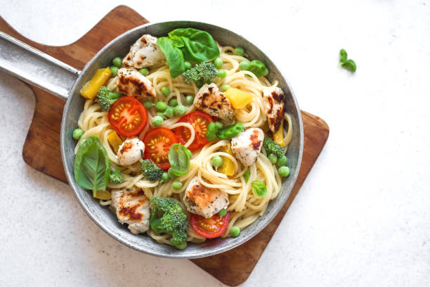 Pasta Primavera Pasta Primavera. Spaghetti pasta with vegetables and basil, top view, copy space. Vegetarian seasonal pasta primavera recipe. primavera stock pictures, royalty-free photos & images