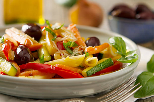Pasta Primavera Pasta primavera made with garden fresh carrots, zucchini, and bell peppers. Served with rigatoni and topped with kalamata olives, basil, and grated parmesan cheese. primavera stock pictures, royalty-free photos & images