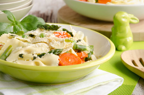 Pasta primavera Fresh bow-tie pasta served on a green plate with carrot, asparagus, onions, peas and parmesan with a green bunny primavera stock pictures, royalty-free photos & images