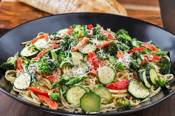 Pasta Primavera with bread A large bowl of Pasta Primavera made with fresh asparagus, broccoli, red bell pepper and zucchini is served with a loaf of Italian bread.  One image in a series. primavera stock pictures, royalty-free photos & images