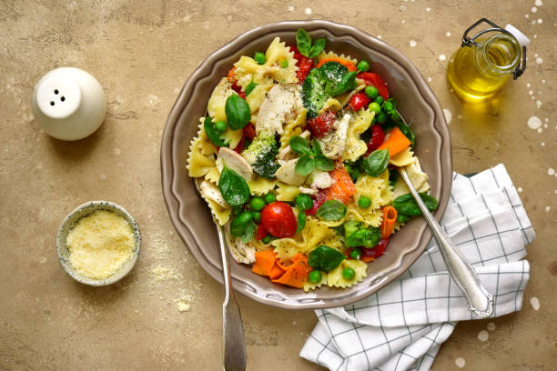 Pasta primavera with chicken in Pasta primavera with chicken in a bowl over beige (sand) slate, stone or concrete background.Top view. primavera stock pictures, royalty-free photos & images