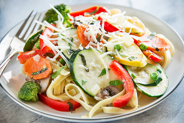 Pasta Primavera with fresh garden vegetables Close-up of a plate full of pasta primavera made with fettuccine and fresh garden vegetables. primavera stock pictures, royalty-free photos & images