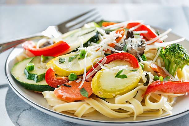 Pasta Primavera with fresh garden vegetables A plate full of delicious pasta primavera made with fettuccine, squash, zucchini, red bell pepper, carrots, peas, broccoli, mushrooms and basil.  It is topped with  freshly grated parmesan cheese. primavera stock pictures, royalty-free photos & images