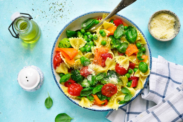 Pasta primavera with spring vegetables Pasta primavera with spring vegetables in a white vintage bowl on a light blue slate, stone or concrete background.Top view. bow tie pasta stock pictures, royalty-free photos & images