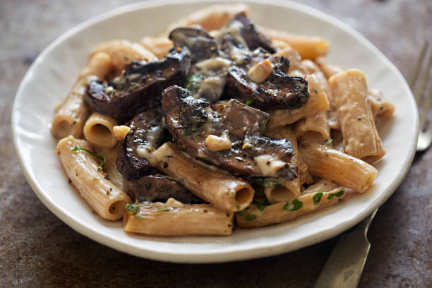 Pasta rigatoni with mushroom sauce and nuts Pasta rigatoni with mushroom sauce and nuts rigatoni stock pictures, royalty-free photos & images