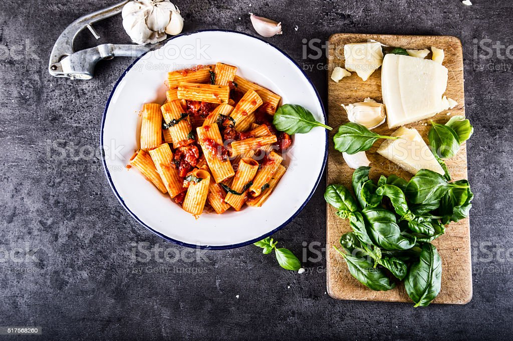 Pasta Rigatoni with tomato sauce basil leaves and parmesan cheese. stock photo