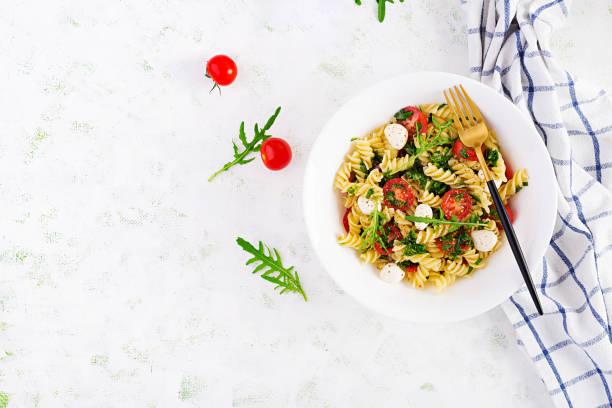 Pasta salad. Fusilli Pasta - Caprese salad with tomato, mozzarella and basil. Top view, flat lay, copy space stock photo