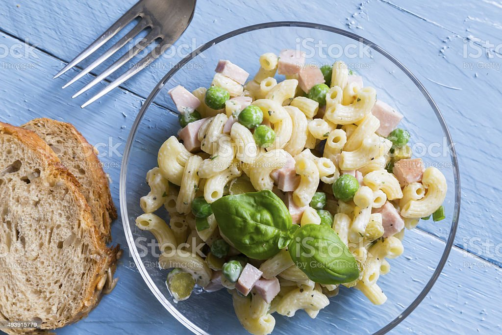 Pasta salad in a glass bowl on blue wood stock photo