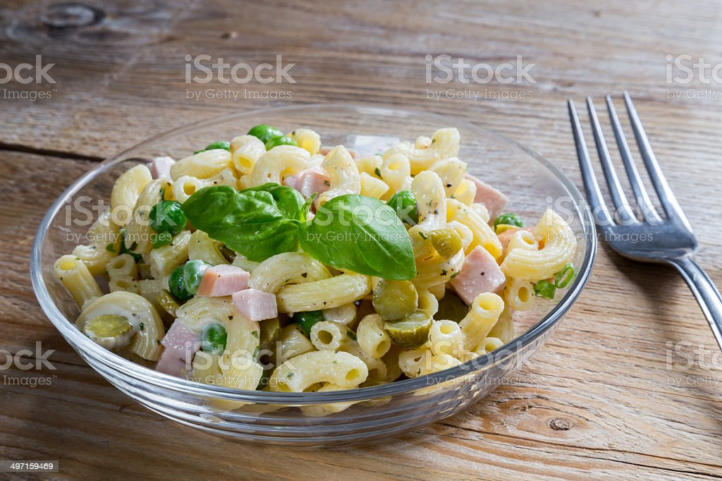 Pasta salad in a glass bowl on wood stock photo