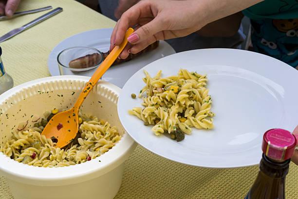 nudelsalat wird auf einer platte - nudelsalat zum grillen stock-fotos und bilder