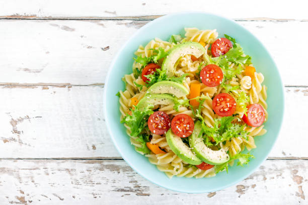 Pasta salad with avocado, fresh tomato, pepper and lettuce, top view stock photo