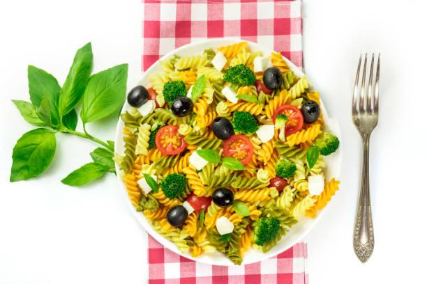 pasta-salat mit basilikum und gabel auf weiß - kariertes hintergrundsbild stock-fotos und bilder