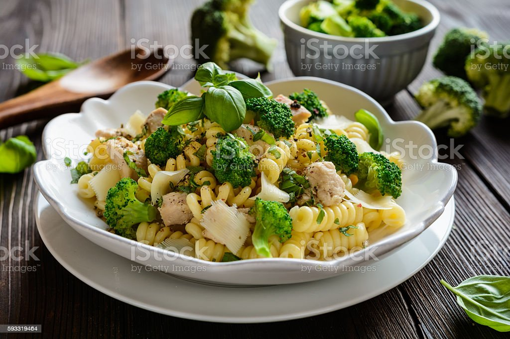 Pasta salad with chicken meat, broccoli, cheese and basil stock photo