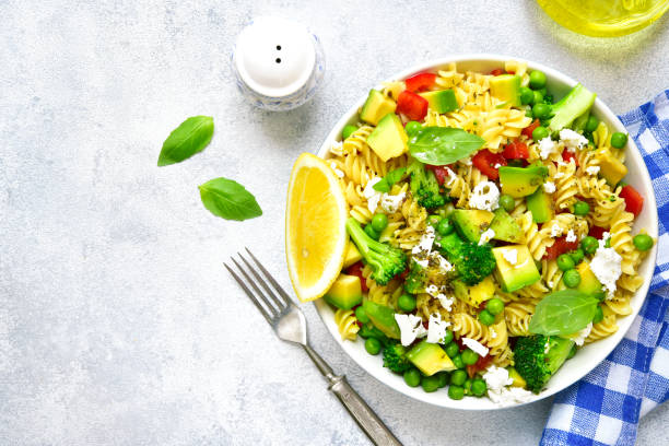Pasta salad with green vegetables and feta.Top view. Pasta salad with green vegetables and feta in a vintage plate on a light concrete,stone or slate background.Top view. primavera stock pictures, royalty-free photos & images