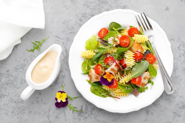 nudelsalat mit gegrilltem hühnerfleisch, gemüse und käse - gesunde huhn pasta stock-fotos und bilder