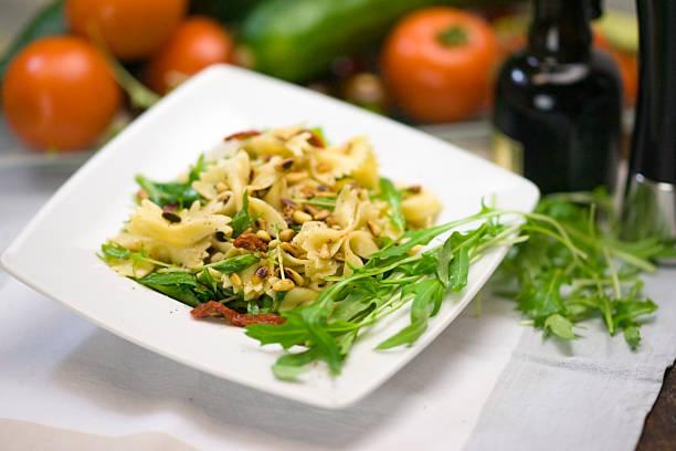 nudelsalat mit getrockneten tomaten und rucola - nudelsalat zum grillen stock-fotos und bilder