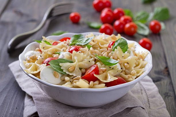 Pasta salad with tomato, mozzarella, pine nuts and basil Pasta salad with tomato, mozzarella, pine nuts and basil in a white ceramic bowl on a wooden table bow tie pasta stock pictures, royalty-free photos & images