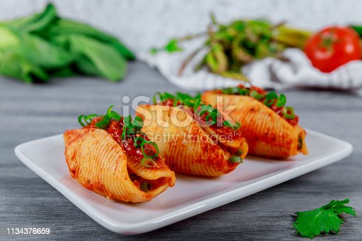 Shells pasta stuffed with minced beef meat with herbs and tomato sauce