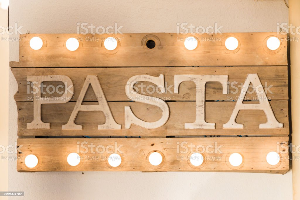 Pasta sign made of wooden planks and light bulbs on top and bottom stock photo