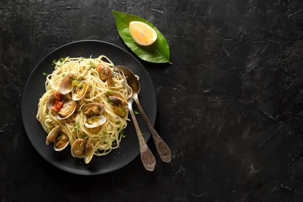 pasta spaghetti alle vongole seafood pasta med tomater i svart tallrik serveras med vintage bestick och citron på svart bakgrund kopieringsutrymme - pasta vongole bildbanksfoton och bilder