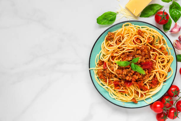 pasta spaghetti bolognese on a blue plate on white marble table. healthy food. view from above pasta spaghetti bolognese on a blue plate on white marble table. healthy food. view from above with copy space spaghetti stock pictures, royalty-free photos & images