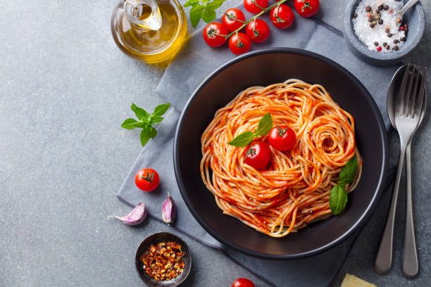 Pasta, spaghetti with tomato sauce in black bowl on grey background. Copy space. Top view. stock photo