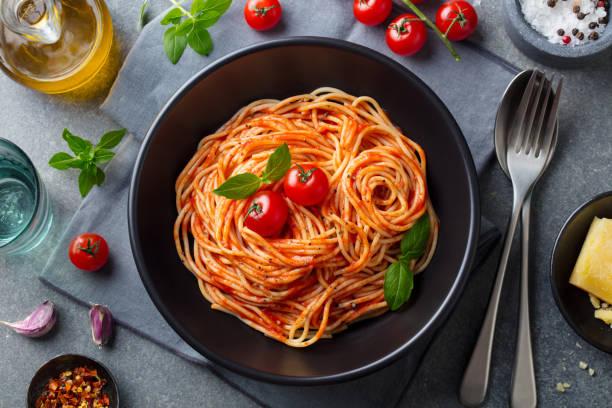 pasta, spaghetti al sugo di pomodoro in ciotola nera su fondo in pietra grigia. vista dall'alto. - pasta foto e immagini stock