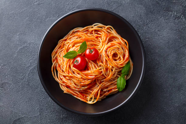 Pasta, spaghetti with tomato sauce in black bowl. Slate background. Top view. stock photo