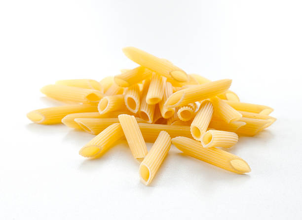 pasta tubes, Penne dry uncooked pasta tubes, penne, on white background rigatoni stock pictures, royalty-free photos & images