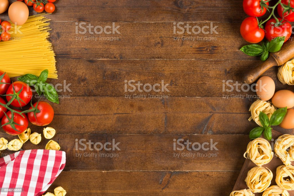 Pasta, vegetables and eggs on table High angle view of pasta, vegetables and eggs on table. Ingredients are arranged on wood. It is representing Italian restaurant background. Abundance Stock Photo