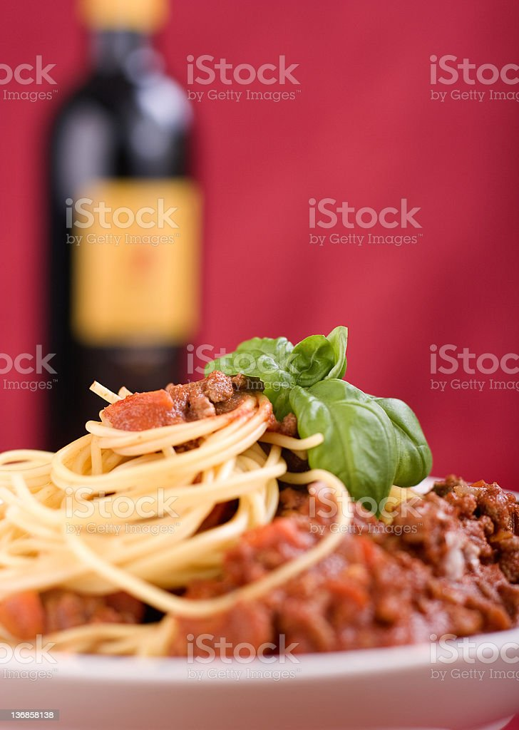 Pasta & Wine A detailed shot of pasta on a red background with a bottle of wine. The background and wine bottle are out of focus. Basil Stock Photo