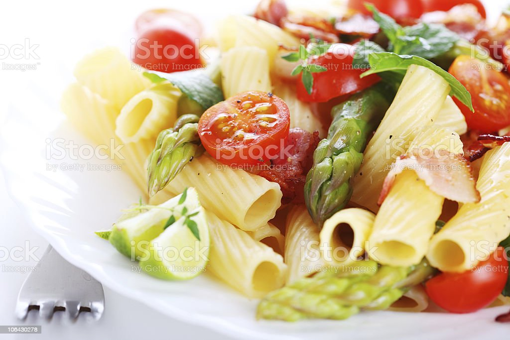 Pasta with asparagus, tomatoes and bacon royalty-free stock photo