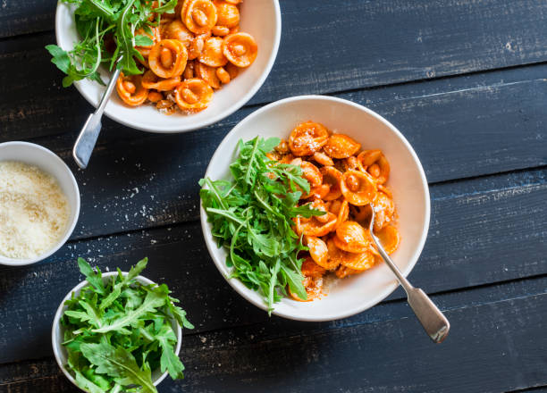 Pasta with beans, tomato sauce, parmesan and arugula on dark background, top view. Vegetarian beans orecchiette pasta Pasta with beans, tomato sauce, parmesan and arugula on dark background, top view. Vegetarian beans orecchiette pasta orecchiette stock pictures, royalty-free photos & images