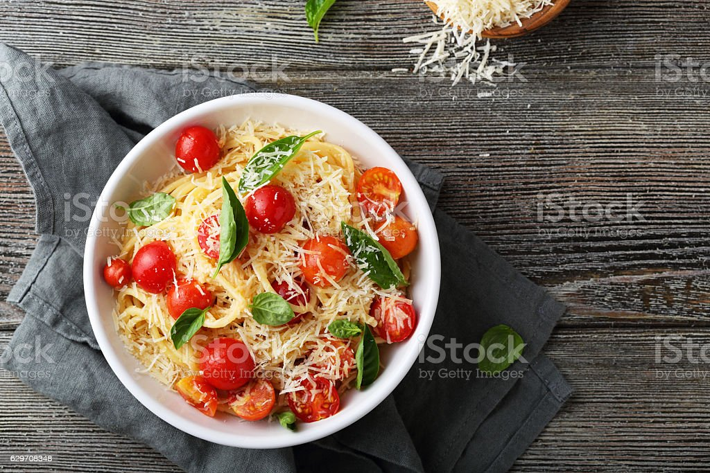 pasta with cheese and tomato on wood stock photo