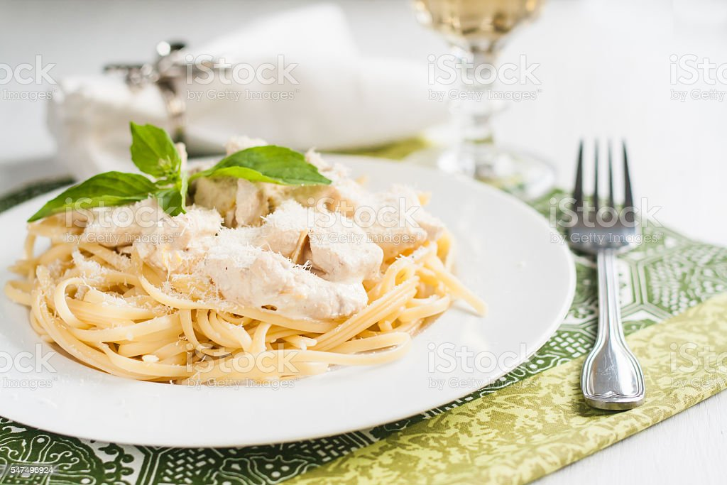 Pasta with chicken, cheese, basil serving wine stock photo