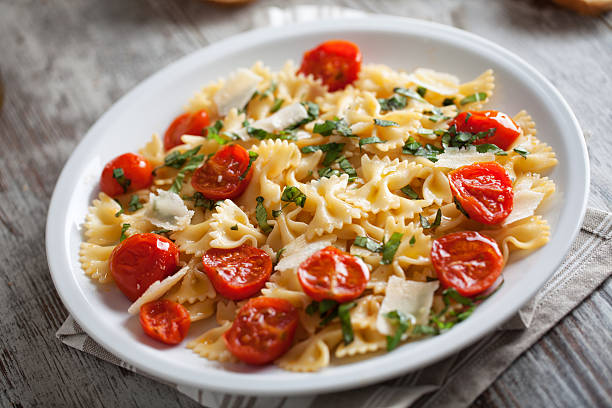 Pasta with fresh tomatoes and basil Pasta with fresh tomatoes and basil bow tie pasta stock pictures, royalty-free photos & images