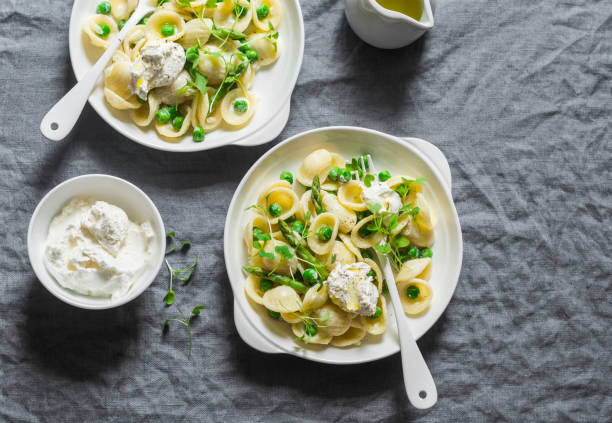 Pasta with green peas, asparagus and fresh ricotta. On a gray background, top view. Healthy delicious food Pasta with green peas, asparagus and fresh ricotta. On a gray background, top view. Healthy delicious food orecchiette stock pictures, royalty-free photos & images