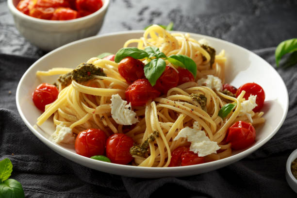 pasta con salsa de pesto verde, tomates asados y queso mozzarella en plato blanco sobre fondo oscuro rústico - comida italiana fotografías e imágenes de stock