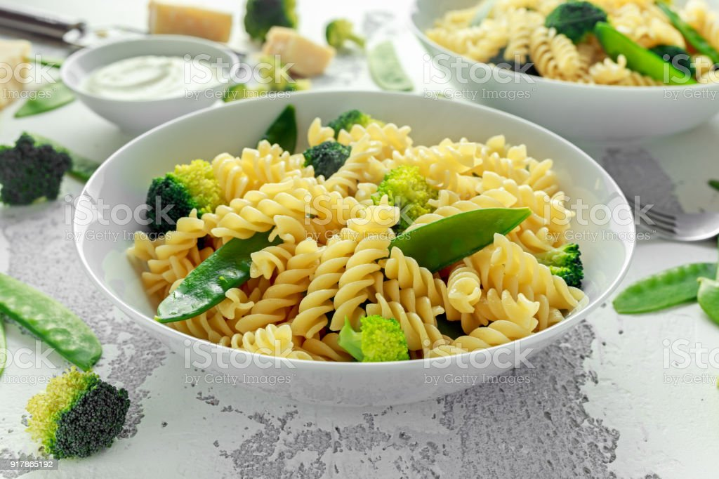 Pasta with green vegetables broccoli, Mange tout and creamy sauce in white plate stock photo