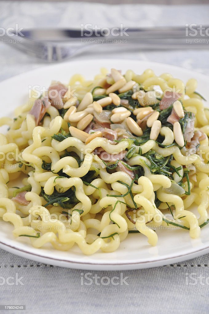 Pasta with herbs, bacon and pine nuts royalty-free stock photo