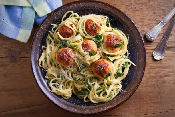 pasta mit hackbällchen und spinat. spaghetti mit fleischbällchen in schüssel auf holztisch - spaghetti mit spinat stock-fotos und bilder
